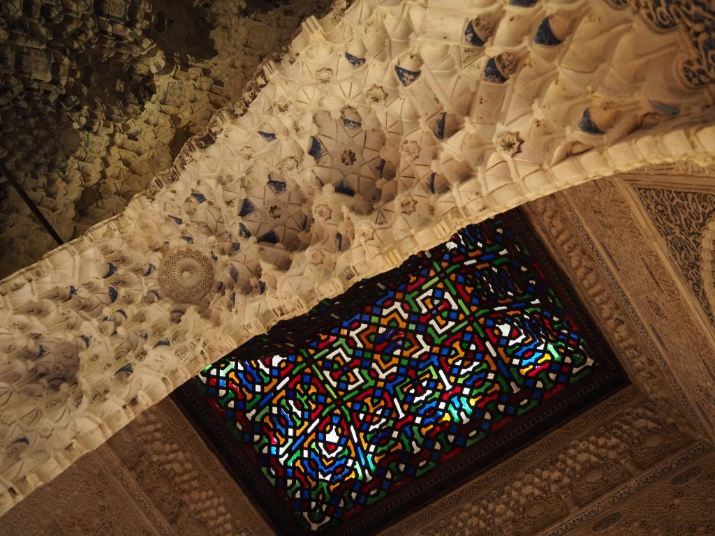 Die bunten Glasscheiben, die in einen feinen Holzrahmen eingelassen sind, vergießen vielfarbiges Licht in einem Bereich, der einst Thronsaal gewesen sein mochte.