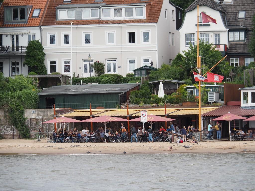 Strandperle - das wohl bekannteste Büdchen Hamburgs. Gelber Sand, leichte Brise und dicke Pötte fahren vorbei. Hamburg pur!